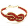 Golden grass bracelet with red infinity design